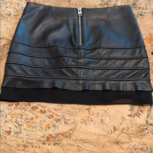 Black leather mini skirt with lower sheet panel